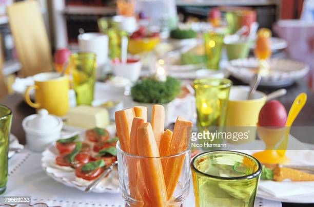 Easter table setting, focus on carrot slices in glass