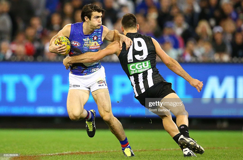 Easton Wood of the Bulldogs is tackled by Levi Greenwood of the Magpies during the round 10 AFL match between the Collingwood Magpies and the Western Bulldogs at Melbourne Cricket Ground on May 29, 2016 in Melbourne, Australia.