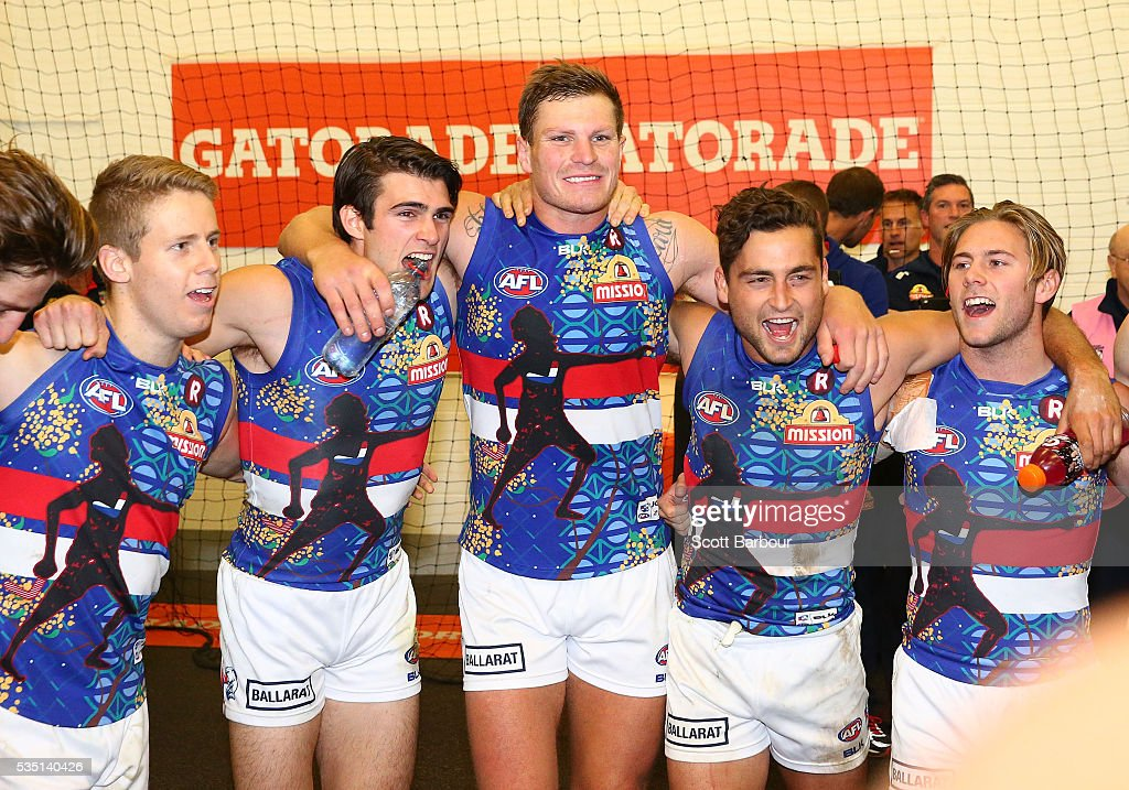 Easton Wood of the Bulldogs, Jack Redpath of the Bulldogs and <a gi-track='captionPersonalityLinkClicked' href=/galleries/search?phrase=Luke+Dahlhaus&family=editorial&specificpeople=6892749 ng-click='$event.stopPropagation()'>Luke Dahlhaus</a> of the Bulldogs sing the song in the rooms after winning during the round 10 AFL match between the Collingwood Magpies and the Western Bulldogs at Melbourne Cricket Ground on May 29, 2016 in Melbourne, Australia.