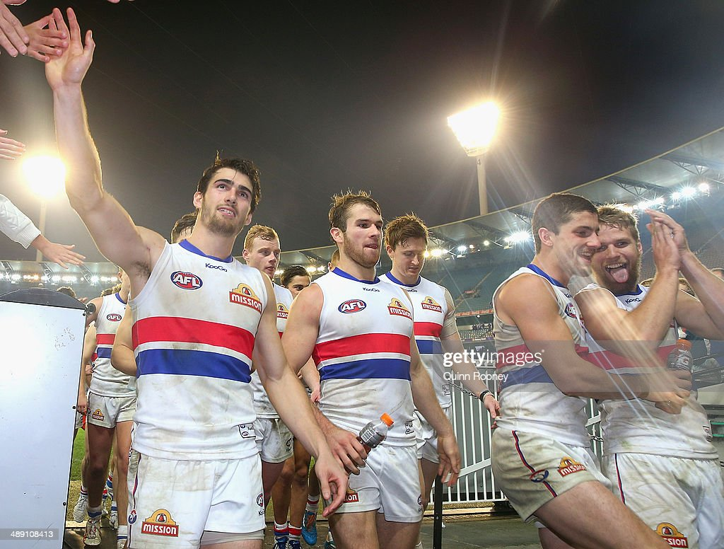 Easton Wood, Stewart Crameri, Tom Liberatore and Jake Stringer of the Bulldogs celebrate as they come off the field after winning the round eight AFL match between the Melbourne Demons and the Western Bulldogs at Melbourne Cricket Ground on May 10, 2014 in Melbourne, Australia.