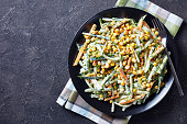 cucumber corn cheese salad with yogurt lemon dressing sprinkled with finely chopped dill on a black plate on a concrete table, view from above, flat lay, close-up, copy space