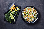 easy cucumber corn cheese salad with yogurt lemon dressing sprinkled with finely chopped dill on a black plate, on a concrete table with ingredients on a cutting board, view from above, flat lay