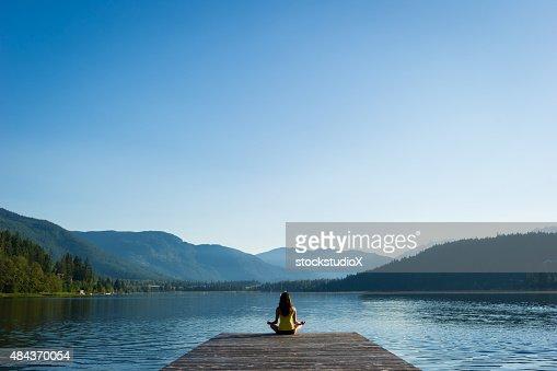 穏やかな湖畔の簡単なポーズでの瞑想の日の出