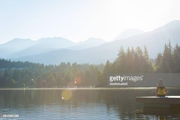 Fácil postura de meditación al atardecer apacible a orillas del lago