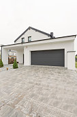 Contemporary detached house with garage seen from a vast concrete driveway