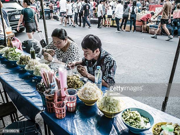 Eating at street food stand Chatuchak market Bangkok