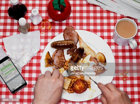 Eating English Breakfast, tea and mobile on table