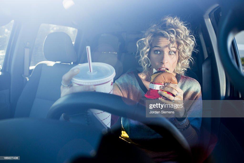 Eating fast food hamburgers and driving. : Stock Photo