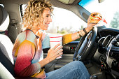 Eating fast food hamburgers and driving.