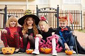 Four little friends in Halloween costumes eating their treats