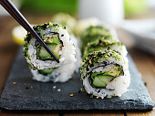 eating healthy kale and avocado sushi roll with chopsticks