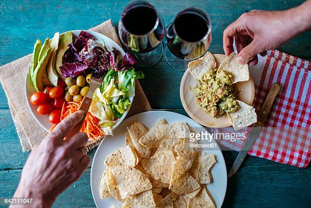 Eating nachos with guacamole and mixed salad