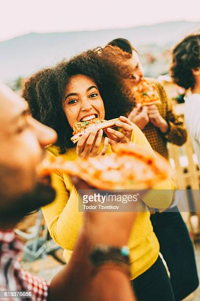 Eating pizza at a party on the roof