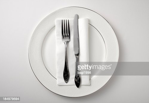 Eating utensils on a white plate against a white background
