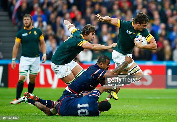 Eben Etzebeth of South Africa is stopped by Samu Manoa and Shalom Suniula of the United States during the 2015 Rugby World Cup Pool B match between...
