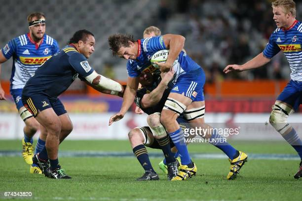 Eben Etzebeth of the Western Stormers is held in a tackle by Liam Squire of the Otago Highlanders during the Super Rugby match between the Otago...
