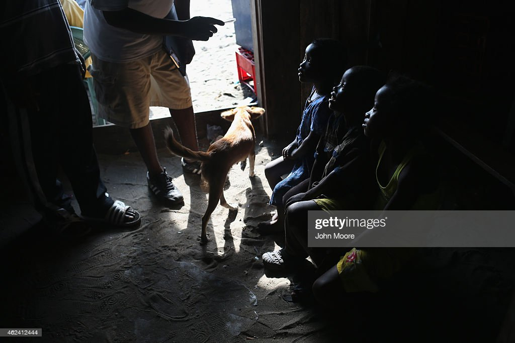 Ebola contact tracing coordinator John Mbayoh speaks with children who's father died just two days before in the West Point township on January 24...