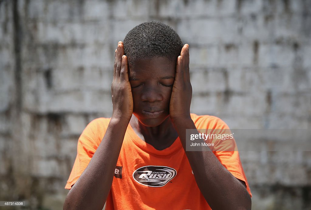 Ebola survivor Jeremra Cooper wipes his face from the heat while in the lowrisk section of the Doctors Without Borders Ebola treatment center on...