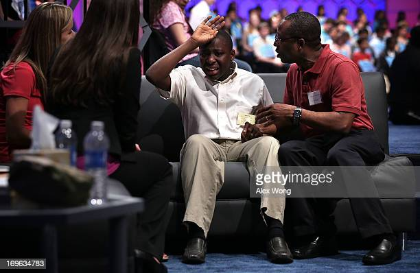 Eboseremhen Eigbe of Galloway New Jersey is comforted by his father after he misspelled the word 'meiosis' and was eliminated in the round three of...