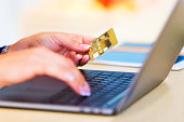 E-business, online shopping and internet payments concept: young woman working on her laptop or notebook and holding a gold credit card in her hand