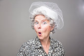 eccentric senior woman, wearing old fashioned clothes and a white hat, with surprised expression