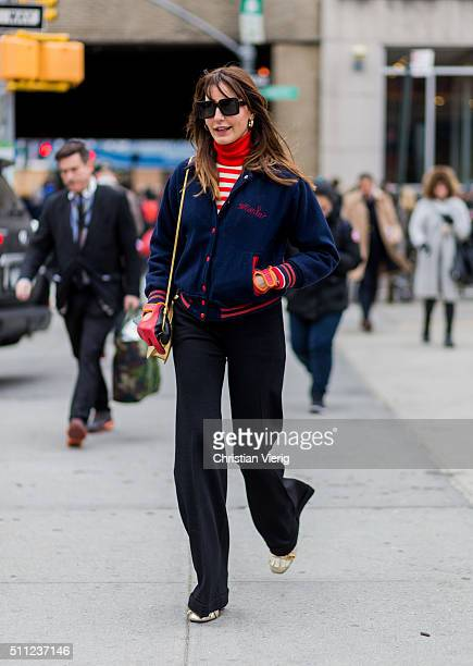 Ece Sukan wearing a golden bag black pants navy jacket and red gloves seen outside Boss during New York Fashion Week Women's Fall/Winter 2016 on...
