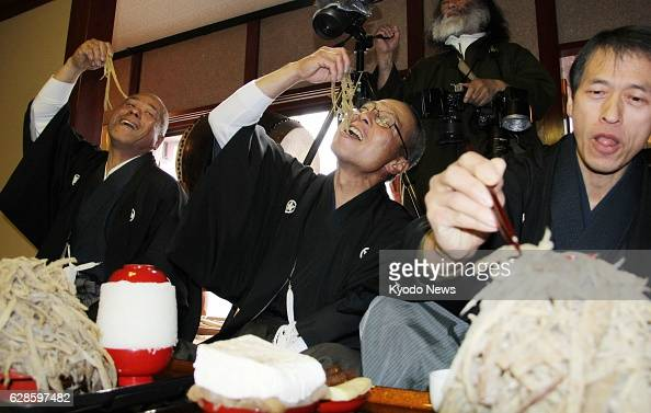 Echizen Japan Men eat piles of sliced burdock root in a traditional festival to wish for a good crop of rice in Echizen Fukui Prefecture central...
