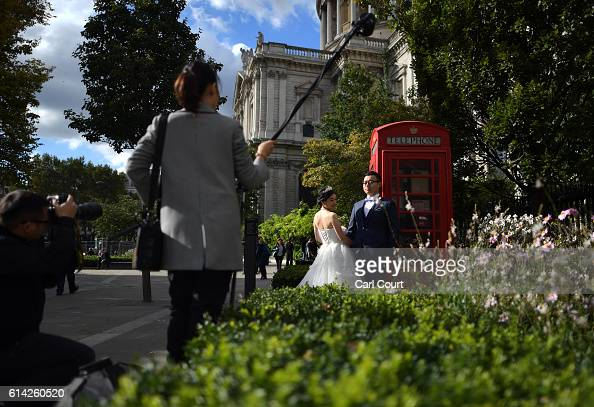 Echo Li and her fiance Charles Qian pose during a prewedding photography shoot next to St Paul's Cathedral on October 11 2016 in London England It's...