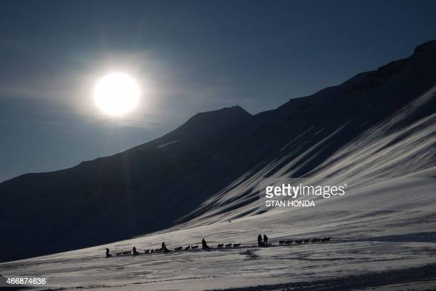 Eclipse watching tourists ride dog sleds outside of Longyearbyen Svalbard an archipeligo administered by Norway on March 19 2015 ahead of the March...