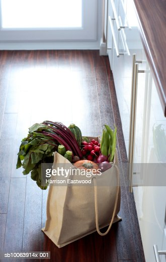 Eco friendly shopping bag filled with vegetables on kitchen floor : Stock Photo