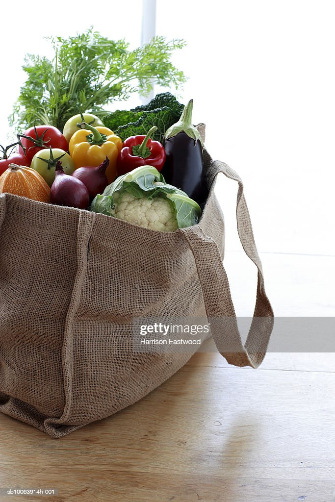Eco friendly shopping bag filled with vegetables on table : Stock Photo