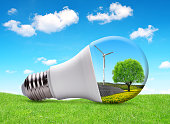Eco LED light bulb with solar panel and wind turbine. The concept of sustainable resources.