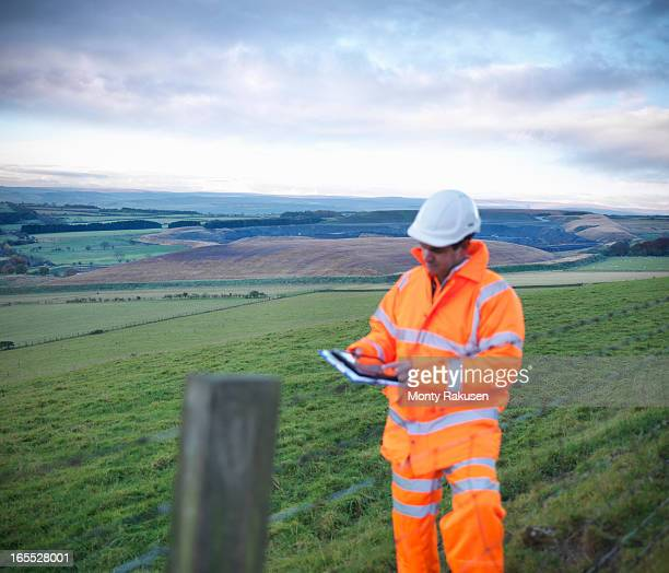 Ecologist using digital tablet inspecting land around surface coal mine site at dawn