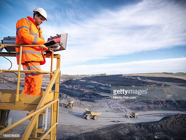 Ecologist using digital tablet surveying surface coal mine site from platform, elevated view