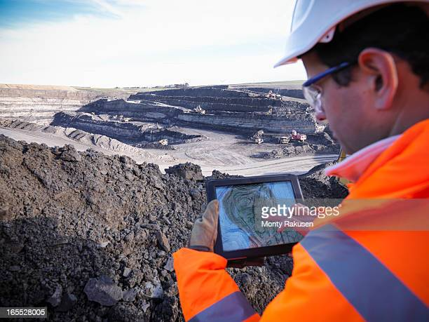 Ecologist using digital tablet surveying surface coal mine site, elevated view