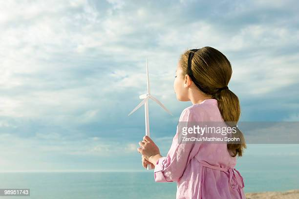 Ecology concept, girl blowing on blades of miniature wind turbine
