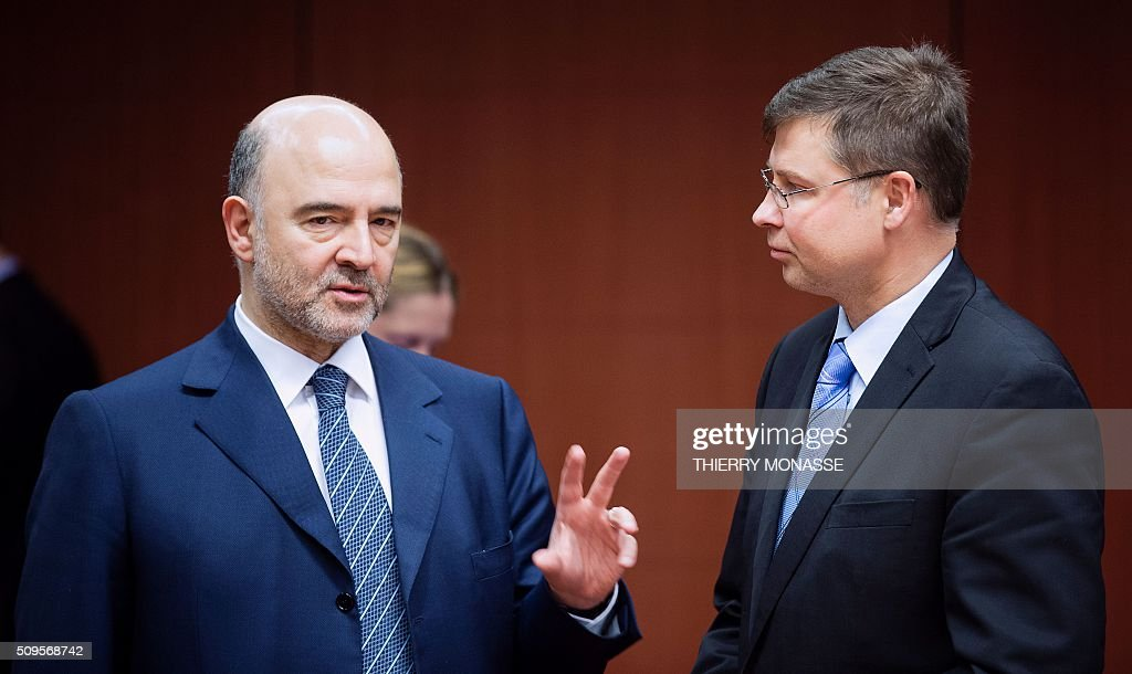 EU Economic and Financial Affairs, Taxation and Customs Commissioner Pierre Moscovici (L) talks with EU Euro and Social Dialogue Commissioner Valdis Dombrovskis (R) prior to a meeting of Eurogroup ministers at the European Council headquarters in Brussels on February 11, 2016. / AFP / THIERRY MONASSE