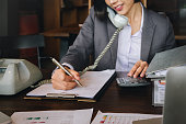 Economist and accountant, female working with document, computer laptop, calculator and using phone contact to customer in office.