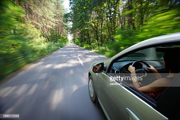 Economy car moving woman driving country road woods trees