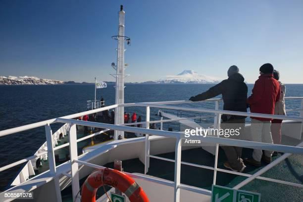 Ecotourists on board of expedition ship m/v Plancius looking at snow covered Beerenberg volcano on Jan Mayen volcanic island in the Arctic Ocean