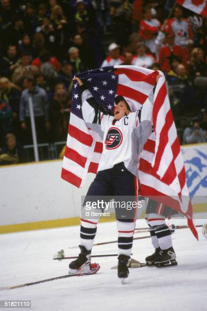 Ecstatic American ice hockey player Cammi Granato of the United States women's hockey team raises an American flag after winning the gold medal game...