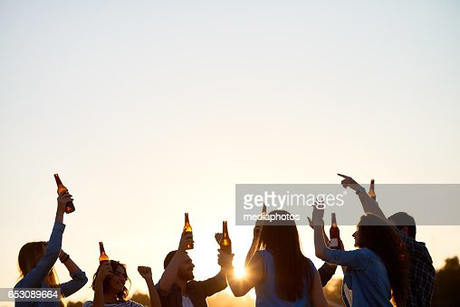 Ecstatic friends dancing with beer : Stock Photo