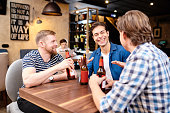Jolly ecstatic young male friends in casual clothing, sitting at table in bar and sharing funny stories while drinking beer together