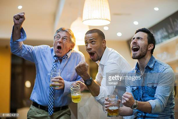 Ecstatic men watching soocer game in a bar after work