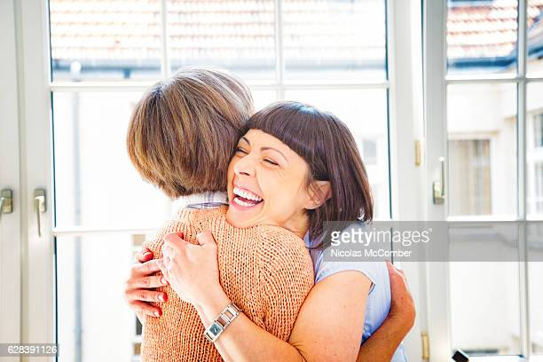 Ecstatic woman hugs her senior mother with a big smile