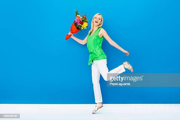 Verzückt Frau springen mit einem Bündel von Blumen