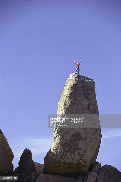 Ecstatic woman rock climbing at Joshua Tree National Park