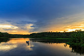 Ecuador, Amazon River region, dugout canoe on Lake Pilchicocha at sunset