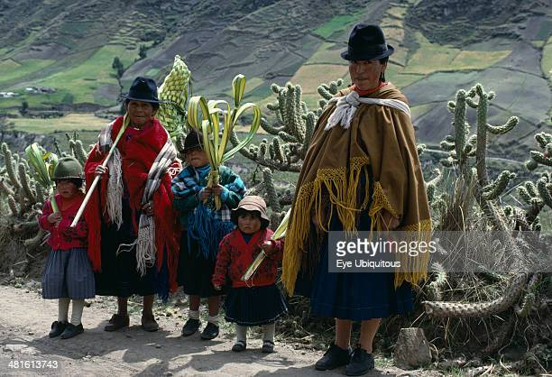 Ecuador Cotopaxi Zumbahua Family on roadside returning home from Palm Sunday Mass holding woven and shaped palm fronds with line of cacti and...