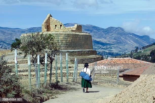 Ecuador, Ingapirca, Temple of the Sun, indigenous woman walking pass wall